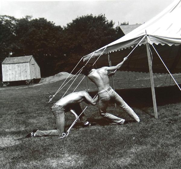 men pulling up a tent